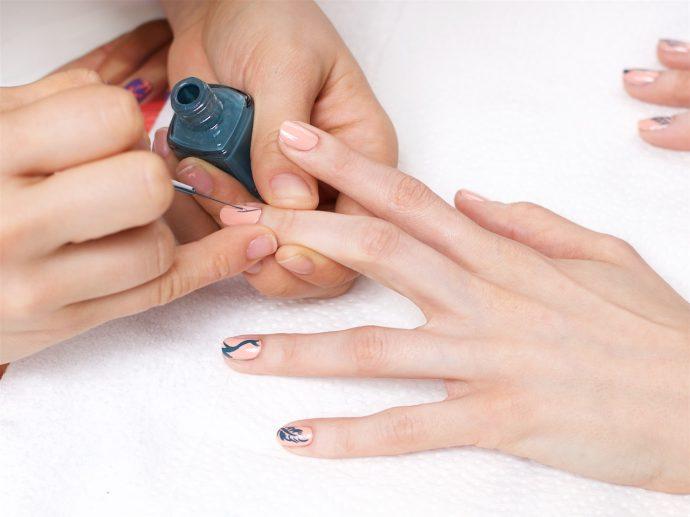 Мастер маникюра рисует на ногтях