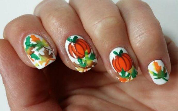 Белый маникюр с оранжевыми тыквами