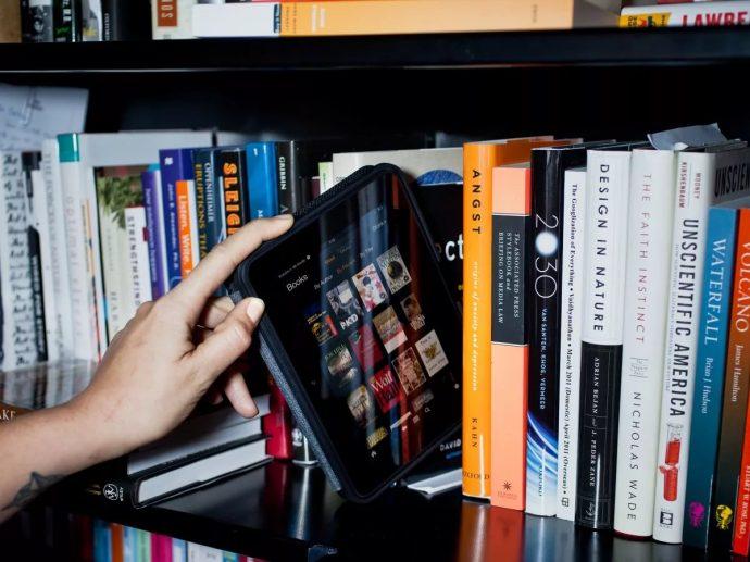 Полка с бумажными книгами и электронной «читалкой»