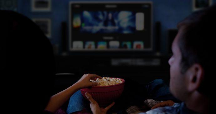 Пара смотрит фильм и ест попкорн