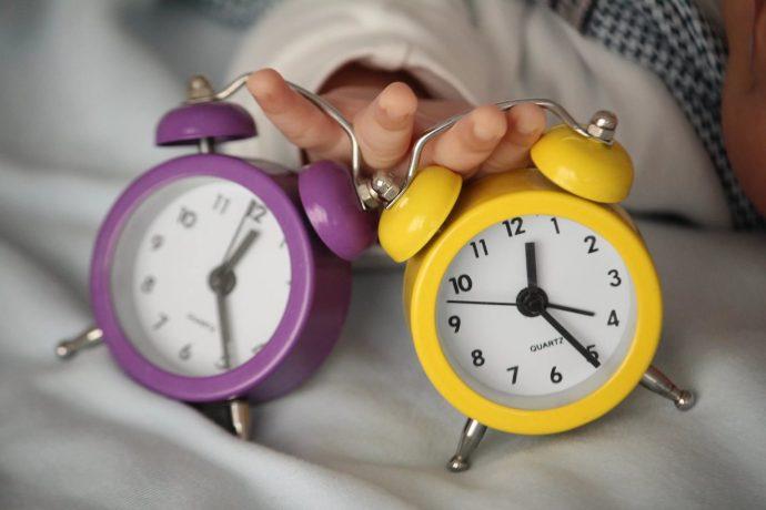 Два будильника жёлтого и фиолетового цветов