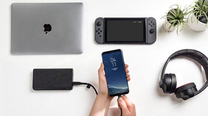 Гаджеты на столе: ноутбук, игровая консоль, наушники, пауэрбанк и телефон