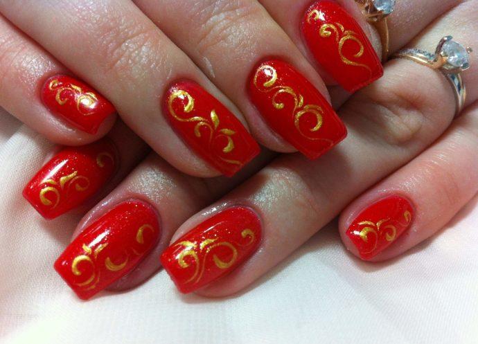 Красные ногти с золотыми вензелями
