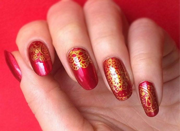 Золотые орнаменты на красных ногтях