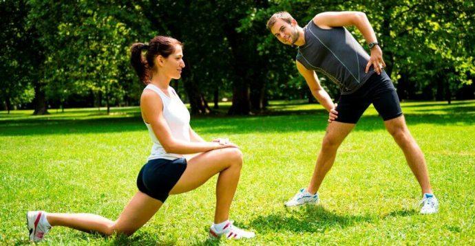 Парень и девушка выполняют разминку перед тренировкой