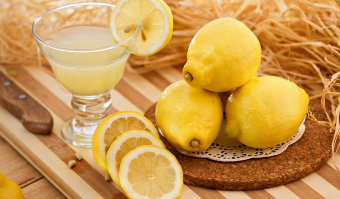 Сок и плоды лимона на столе