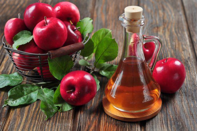 Яблочный уксус в прозрачном графине и яблоки на столе