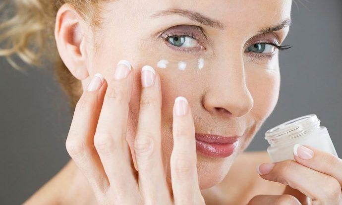 Женщина наносит антивозрастной крем на лицо