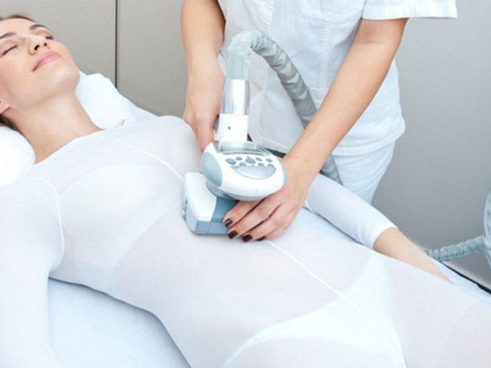Специалист выполняет LPG массаж на животе девушки