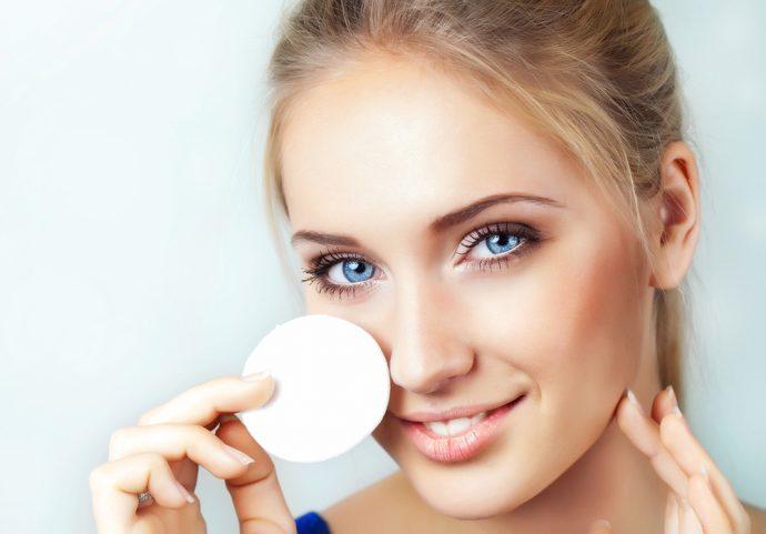 Девушка удаляет косметику с лица ватным диском