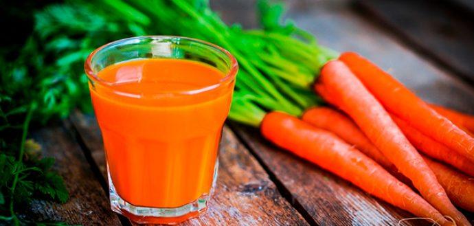 Морковный сок в прозрачном стакане и овощи