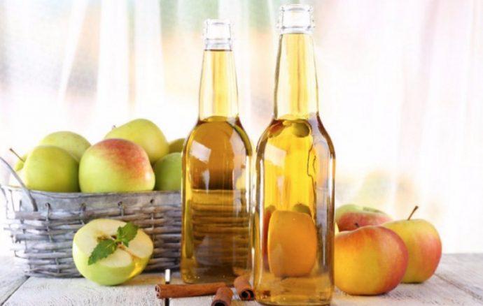 Яблочный уксус в прозрачных бутылках и фрукты