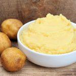 Картофельное пюре в белой пиале и овощи