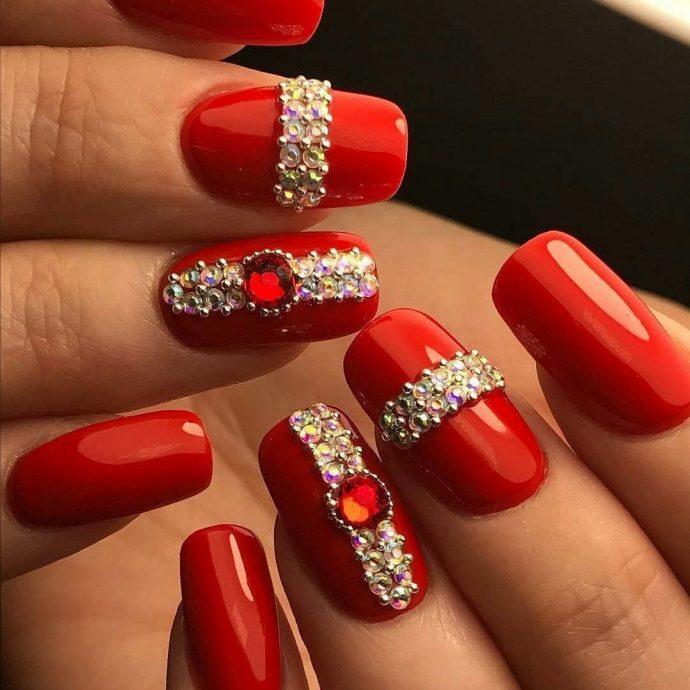 Красный маникюр с серебряными стразами и красным камнем
