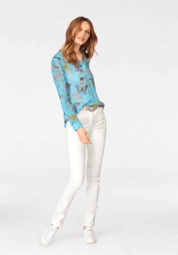 Девушка в джинсах-скинни и блузке с бабочками