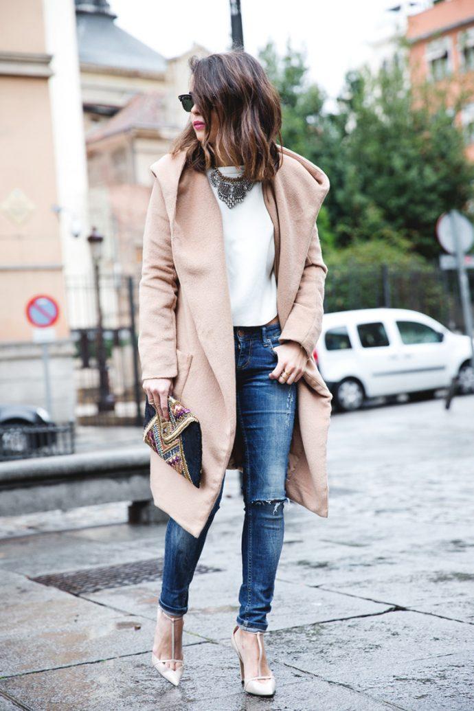 Девушка в джинсах-скинни и светлом пальто