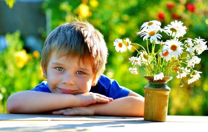 Мальчик с букетом ромашек