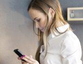 Грустная девушка смотрит на телефон