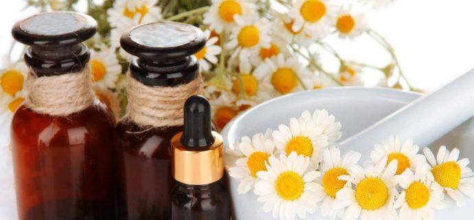 Цветки ромашки и банки с маслами