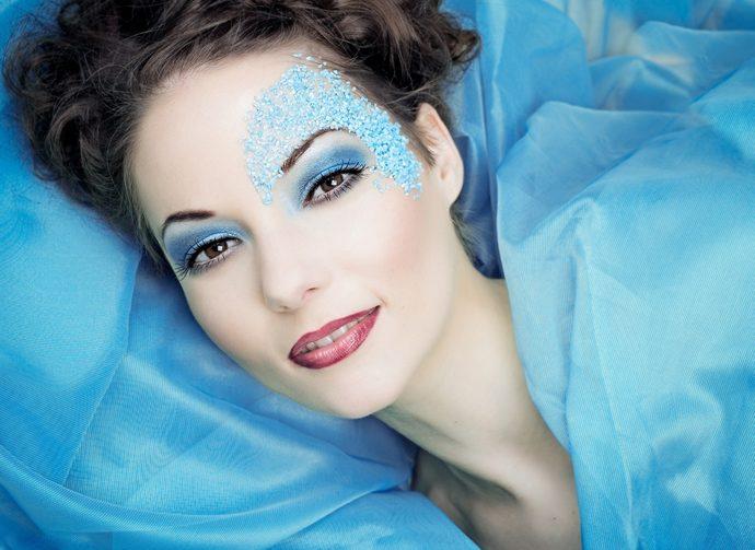 Девушка с голубым макияжем на голубом фоне