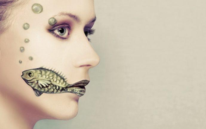 Девушка с рисунком на лице в виде рыбы