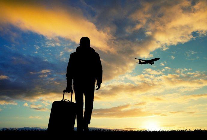 Силуэт человека с чемоданом и самолёта