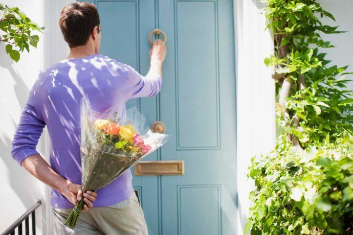 Мужчина с букетом цветов стучит в дверь