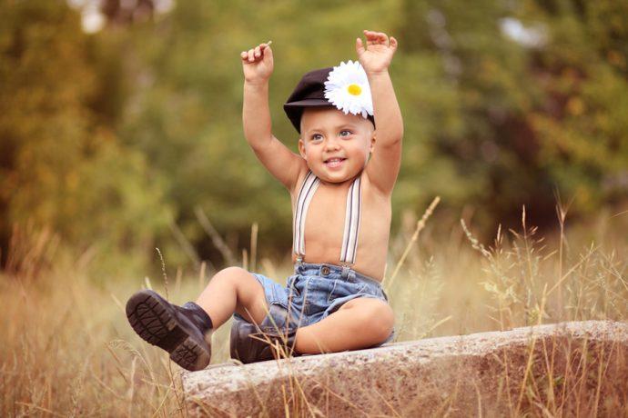 Маленький мальчик в кепке с ромашкой