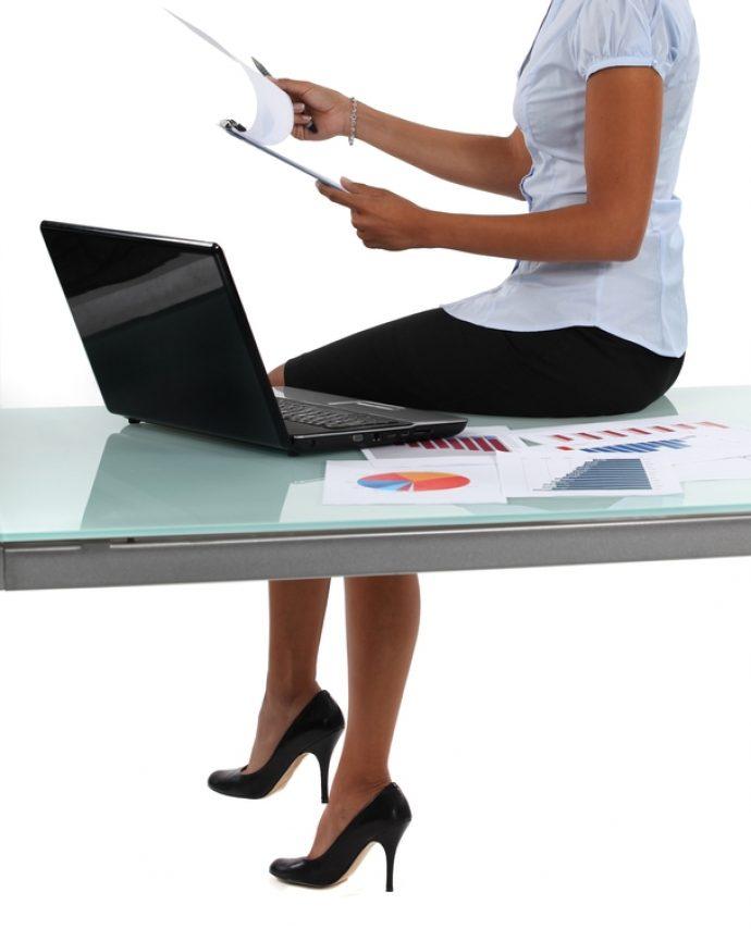 Девушка сидит на офисном столе