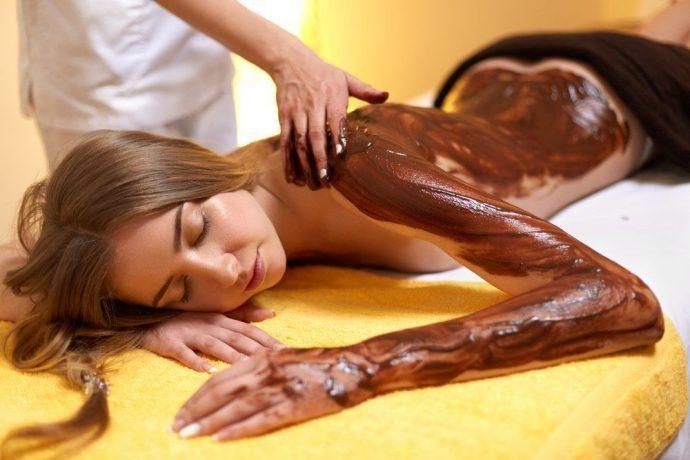 Девушке на тело наносят шоколад