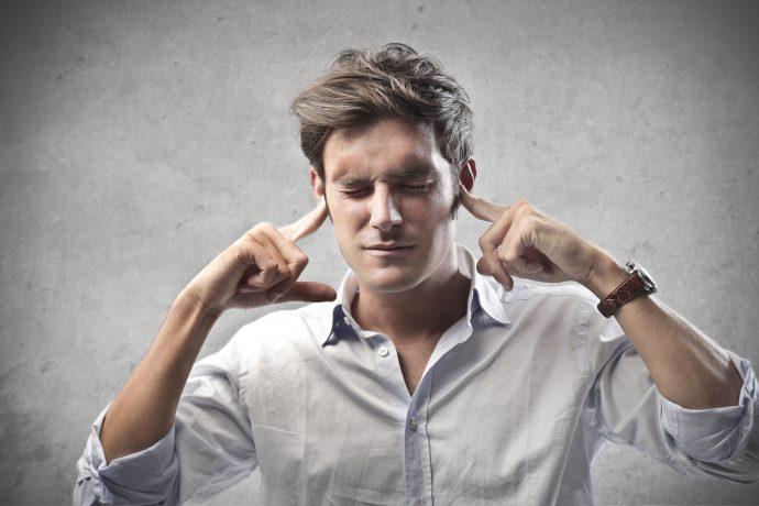 Мужчина закрывает уши