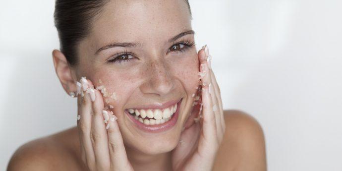 Девушка чистит лицо