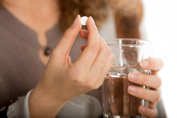 Стакан воды и таблетка в руках