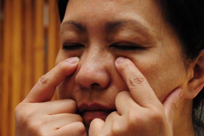 Женщина делает массаж лица