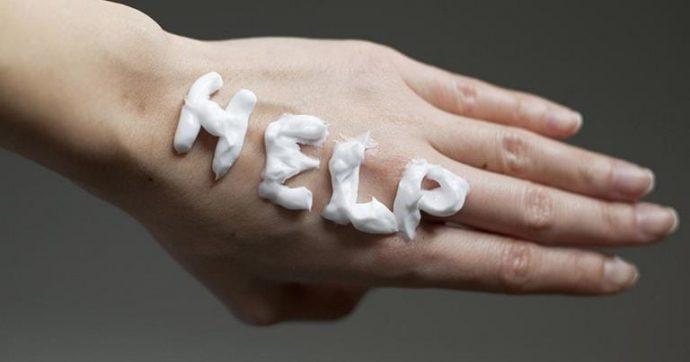 Слово HELP выложено на руке кремом