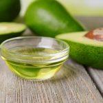 Масло авокадо в прозрачной пиале и плоды в разрезе