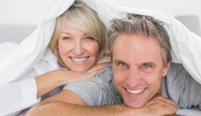 Мужчина и женщина лежат под одеялом