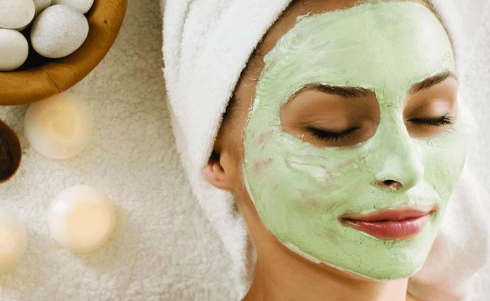 Женщина лежит в ванной и наносит на лицо маску