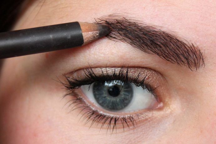 Девушка подкрашивает брови карандашом