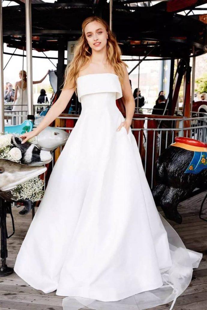 Девушка в свадебном платье с открытыми плечами и шлейфом