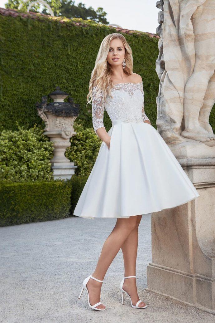 Девушка в коротком пышном свадебном платье с карманами