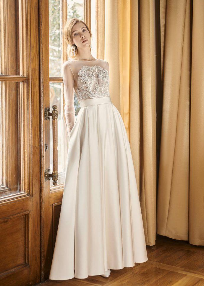 Девушка в лёгком свадебном платье из атласа, сеточки и гипюра