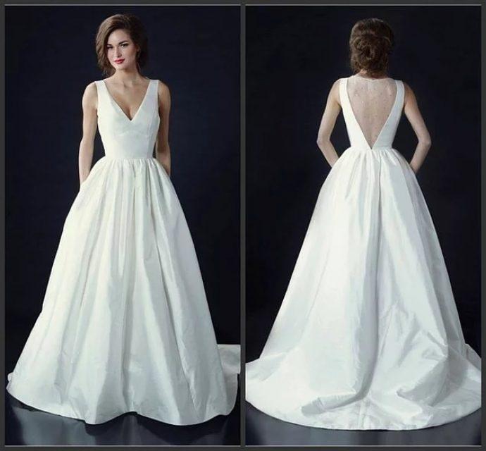 Девушка в элегантном свадебном платье на бретелях с открытой спиной