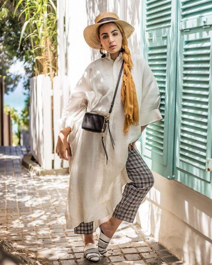 Девушка мусульманка в клетчатых брюках и платье-тенике
