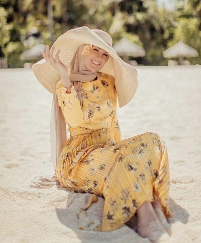 Девушк в ярком платье с цветочным принтов и большой шляпой