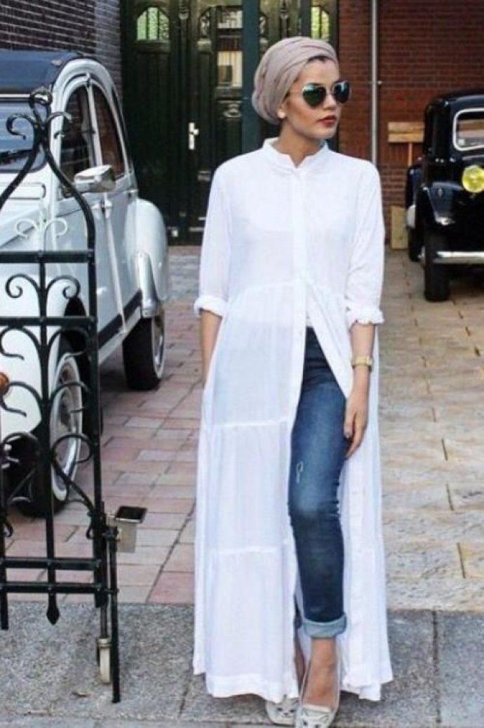 Девушка мусульманка в джинсах и белом платье-халате