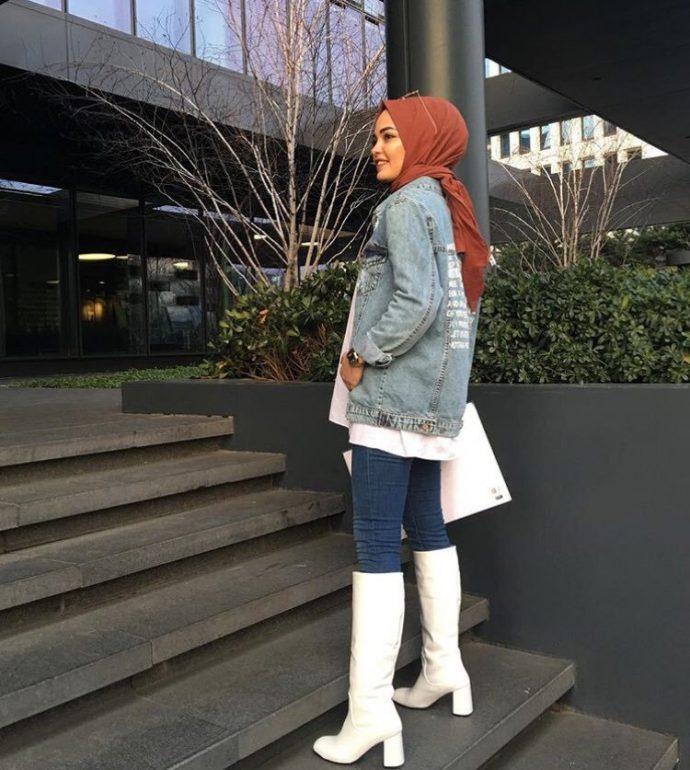Девушка мусульманка в джинсах и джинсовой куртке, белых сапогах и платке
