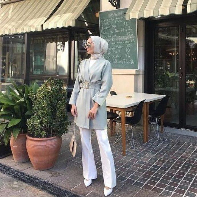 Девушка мусульманка в белых брюках сером тренче