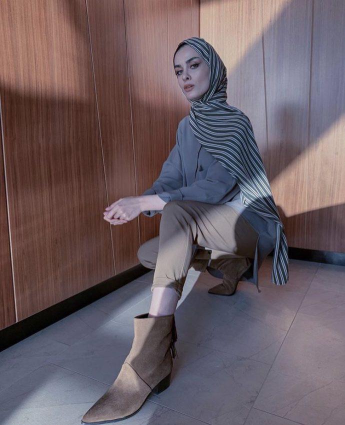 Девушка мусульманка в темно-бежевых брюках и серой блузке