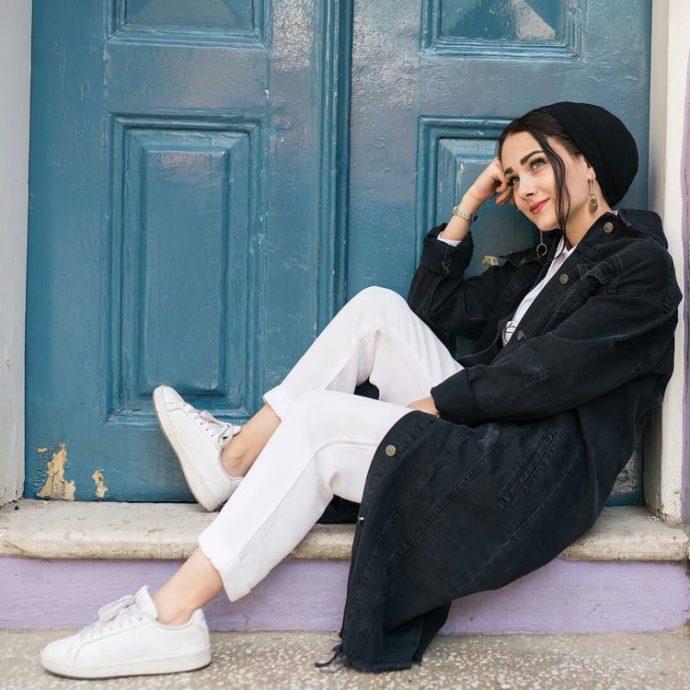 Девушка мусульманка в белых брюках и черном джинсовом пальто